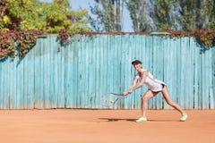 炫耀打在户外背景的女孩羽毛球 有效的生活方式概念 复制空间 免版税图库摄影