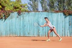 炫耀打在户外背景的女孩羽毛球 有效的生活方式概念 复制空间 免版税库存照片