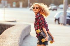 炫耀摆在与滑板的夏天的愉快的女孩 有五颜六色的longboard的时髦的幸运行家妇女在日落 库存照片