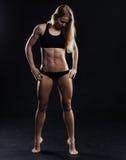 炫耀有强的肌肉的健身妇女在黑背景 图库摄影