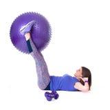 炫耀有pilates球和哑铃的妇女 免版税库存图片