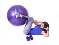 炫耀有pilates球和哑铃的妇女 免版税库存照片