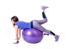 炫耀有pilates球和哑铃的妇女 免版税图库摄影