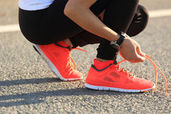 炫耀栓在城市道路的妇女赛跑者鞋带 库存照片