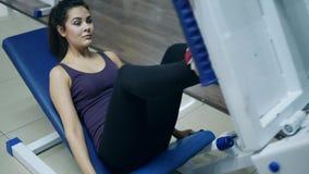 炫耀活动,微笑的女孩训练说谎在腿在健身房的新闻机器 股票录像