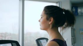 炫耀活动,跑在健身房特写镜头的踏车的愉快的女孩 股票视频