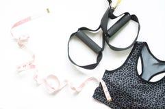 炫耀胸罩、测量磁带和TRX在白色背景,健身和健身房锻炼 免版税图库摄影