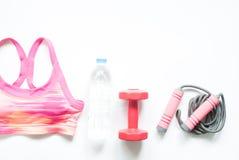 炫耀胸罩、瓶水和在白色背景的健身设备 免版税图库摄影