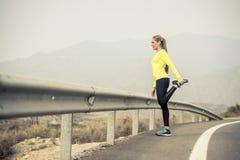 炫耀舒展腿肌肉的妇女在柏油路的连续锻炼以后有干燥沙漠风景的在坚硬健身训练上 库存照片