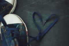 炫耀蓝色牛仔裤起动儿童心脏在织地不很细Grounge Chalckboard的形状鞋带 定调子 教育和育儿 免版税库存照片