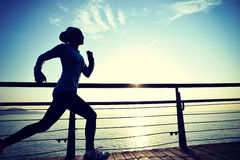 炫耀跑在木木板走道日出海边的妇女 免版税库存图片