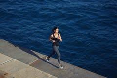 炫耀跑在海浪背景的行动的女孩 免版税库存照片