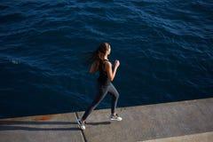 炫耀跑在海浪背景的行动的女孩 免版税库存图片