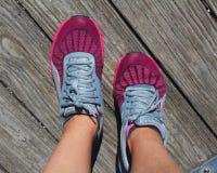 炫耀跑鞋,有一个美丽的自然本底、公园和湖 库存图片