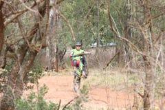 炫耀通过流行的年轻人自行车前轮离地平衡特技在登山车种族 库存图片