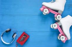 炫耀,健康生活方式,滑旱冰背景 白溜冰鞋、耳机和葡萄酒录音磁带播放机 平的位置,顶视图 库存图片