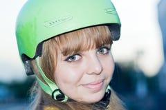 炫耀(骑自行车者,挡雪板)绿色盔甲的年轻美丽的妇女少年 免版税库存照片