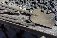 炭烬和铁锹的钳子从中世纪伪造的煤炭的 免版税库存图片