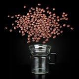 炸开咖啡豆云彩在玻璃杯子的 库存图片