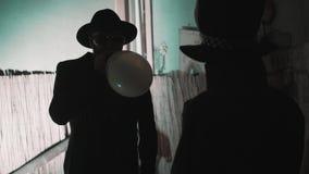炸毁一次气球和谈话与人的帽子的人高顶丝质礼帽的在低落点燃了室 股票录像