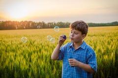 炸毁在领域的平静的男孩肥皂泡在日落 免版税图库摄影