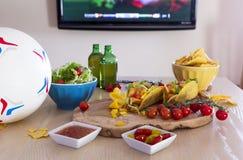 炸玉米饼、啤酒和橄榄球 库存照片