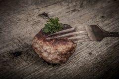 炸肉排和切片在一把叉子在老木桌上 设色 免版税图库摄影