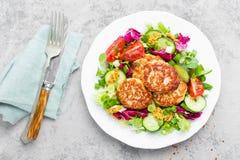 炸肉排和新鲜蔬菜沙拉在白色板材 油煎的丸子用菜沙拉 免版税库存照片