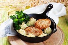 炸肉排用土豆和荷兰芹在长柄浅锅 免版税库存图片