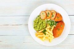 炸薯条、被捣碎的豌豆和鸡炸肉排 免版税库存图片