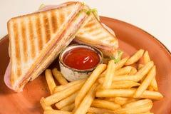 炸薯条和两个三明治与乳酪、香肠和莴苣叶子在一块难看的东西板材,在一架钢琴中间用番茄酱s 免版税库存图片