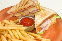 炸薯条和两个三明治与乳酪、香肠和莴苣叶子在一块难看的东西板材,在一架钢琴中间用番茄酱s 库存图片