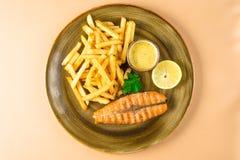 炸薯条和红色片断油煎了与荷兰芹叶子的鱼三文鱼用在一块大板材的调味汁 在棕色背景的顶视图 免版税图库摄影