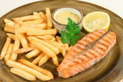 炸薯条和红色片断油煎了与荷兰芹叶子的鱼三文鱼用在一块大板材的调味汁 库存照片