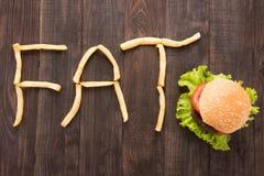 炸薯条用形成在木背景的汉堡词油脂 免版税库存照片