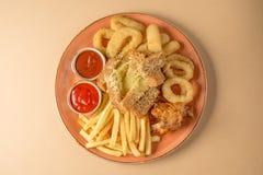 炸薯条,洋葱圈,鸡翼,面包干,对啤酒的一顿快餐在一块大板材用在棕色背景的两个调味汁 顶视图 免版税库存图片