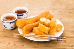 炸面包棍子或您Tiao服务用在木桌上的中国茶 图库摄影