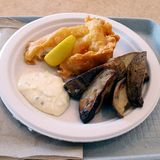 炸鱼加炸土豆片用调味汁和柠檬 免版税图库摄影