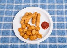 炸鱼排和土豆在白色板材喘气 库存照片