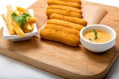 炸鱼排在面团和面包屑被油炸在一个木板用炸薯条和调味汁 免版税库存照片