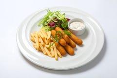 炸鱼排用调味汁、油煎的土豆和新鲜的沙拉莴苣在一块白色板材 图库摄影