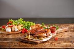 炸鸡与装饰与新鲜蔬菜的被烘烤的年轻土豆 在木背景的开胃静物画 免版税库存图片