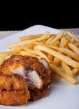 炸鸡和油煎的土豆在板材和黑背景 免版税库存照片