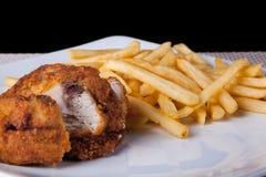 炸鸡和油煎的土豆在板材和黑背景 图库摄影