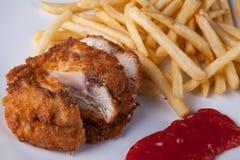 炸鸡和油煎的土豆用辣味番茄酱 库存照片