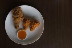 炸鸡和调味汁在一顿白色板材低灯或曝光不足的,炸鸡早餐,特写镜头炸鸡 库存照片
