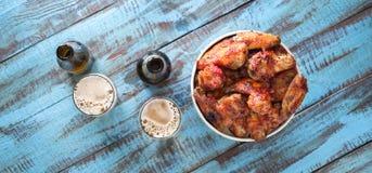 炸鸡在桌上的纸桶飞过用啤酒 免版税库存照片