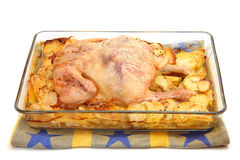 炸鸡用在一个玻璃烤盘的土豆 库存照片