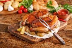 炸鸡用被烘烤的年轻土豆装饰  鸡烟草和一把精妙的叉子 在木bac的开胃静物画 免版税库存照片