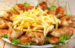 炸鸡腿、土豆和菜在木桌上 库存照片